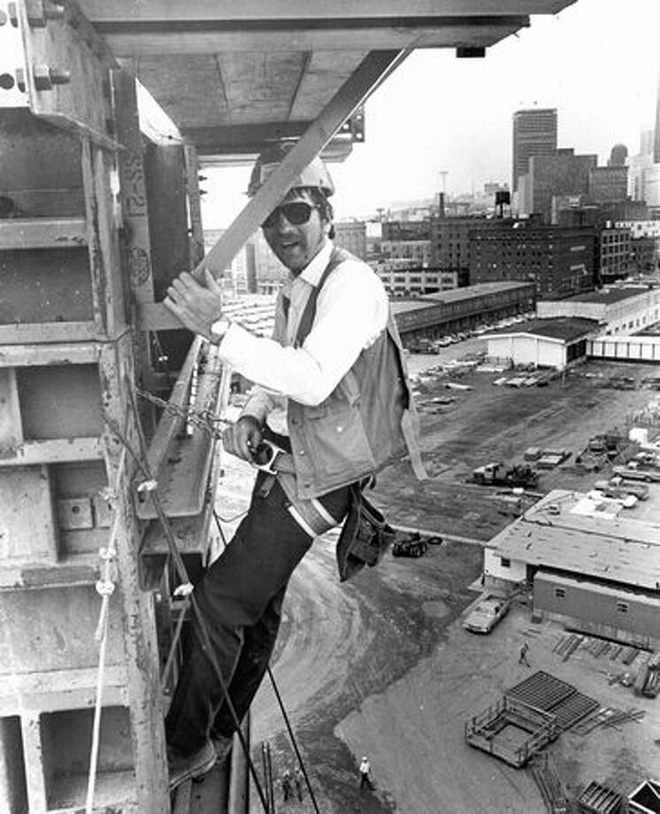 The December 1975 photo caption read: A worker high up on a pillar looks a bit startled at the P-I photographer swung by in a buck raised by one of the huge cranes on the job. Photo: P-I File