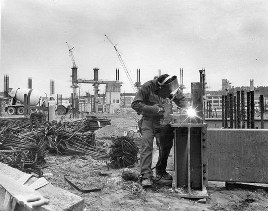 A welder joins steel at the top of a pillar foundation in preparation to form a concrete support, June 26, 1973. Photo: P-I File