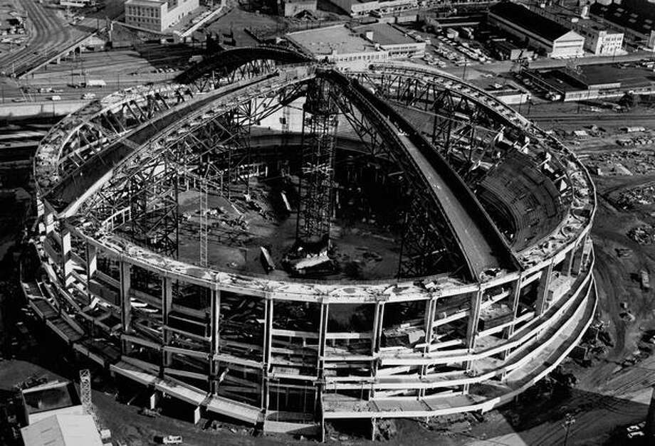 The November 1974 photo caption read: A significant stage of construction has been reached at the King county domed stadium, where workmen have been finishing four of the eventual 40 sections of the concrete roof. Photo: P-I File