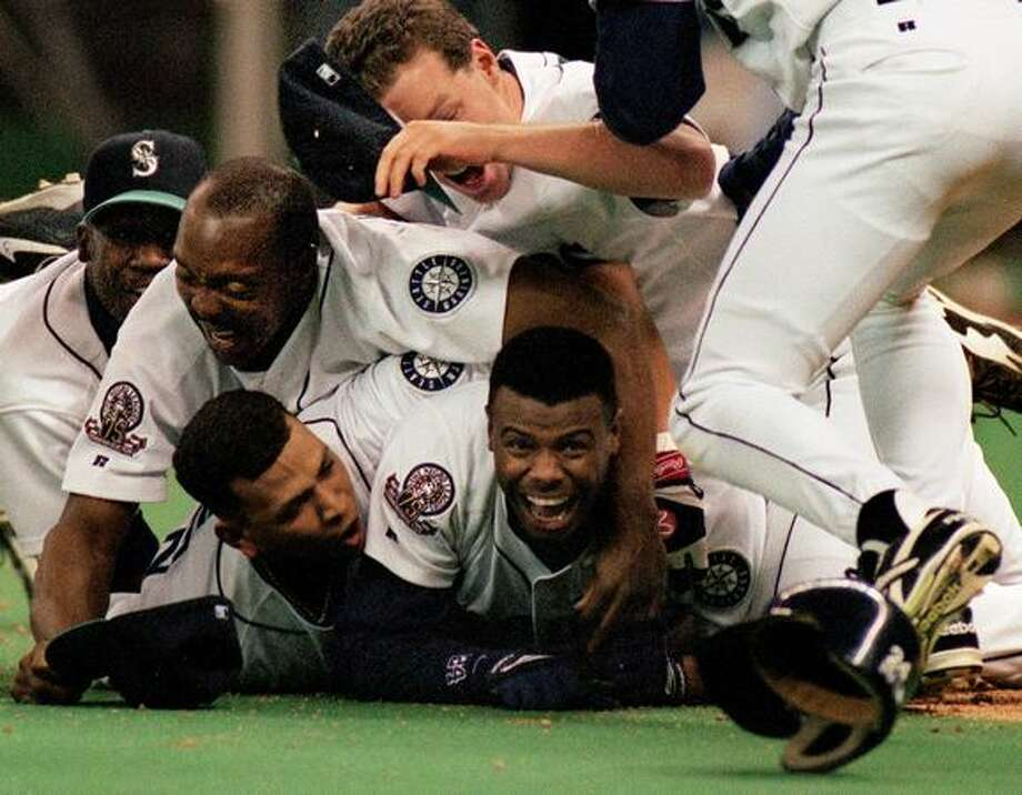 In what's considered the greatest sports moment at the Kingdome, Ken Griffey Jr. smiles after scoring the winning run against the New York Yankees in the 1995 American League Division Series, Oct. 8, 1995. (Robin Layton/Seattlepi.com file) Photo: P-I File
