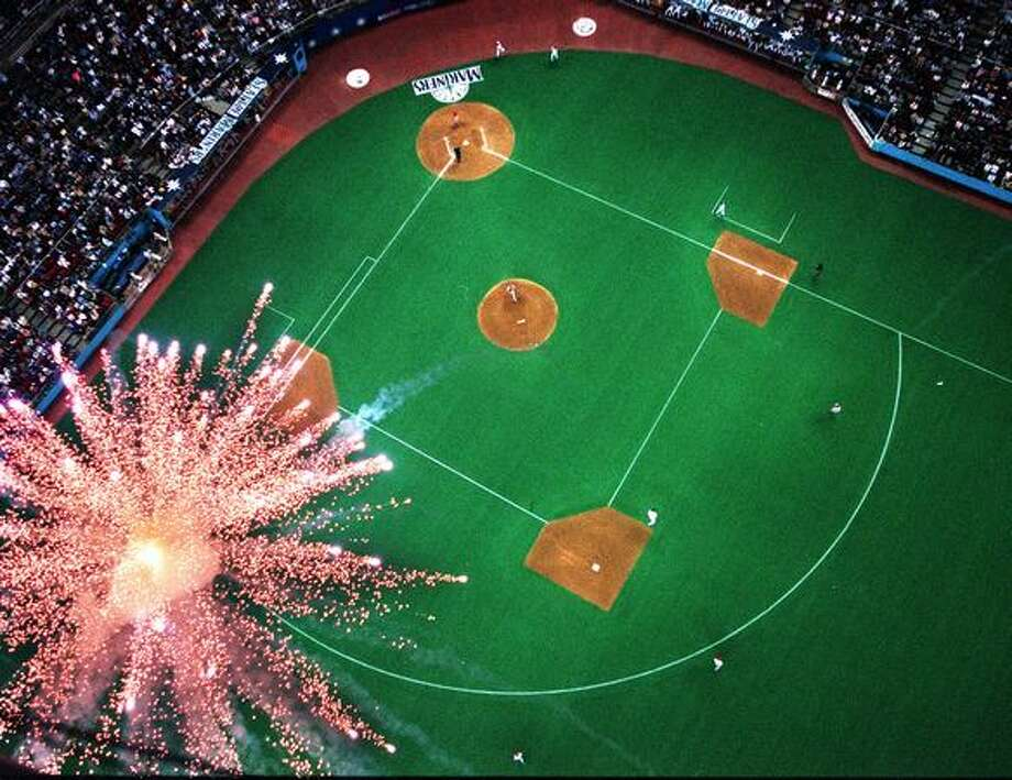 This photo, shot from the roof of the Kingdome, shows a firework exploding as Seattle Mariners David Segui rounds 2nd base. Segui had a sixth inning home run against the Texas Rangers, June 25, 1999. Photo: P-I File