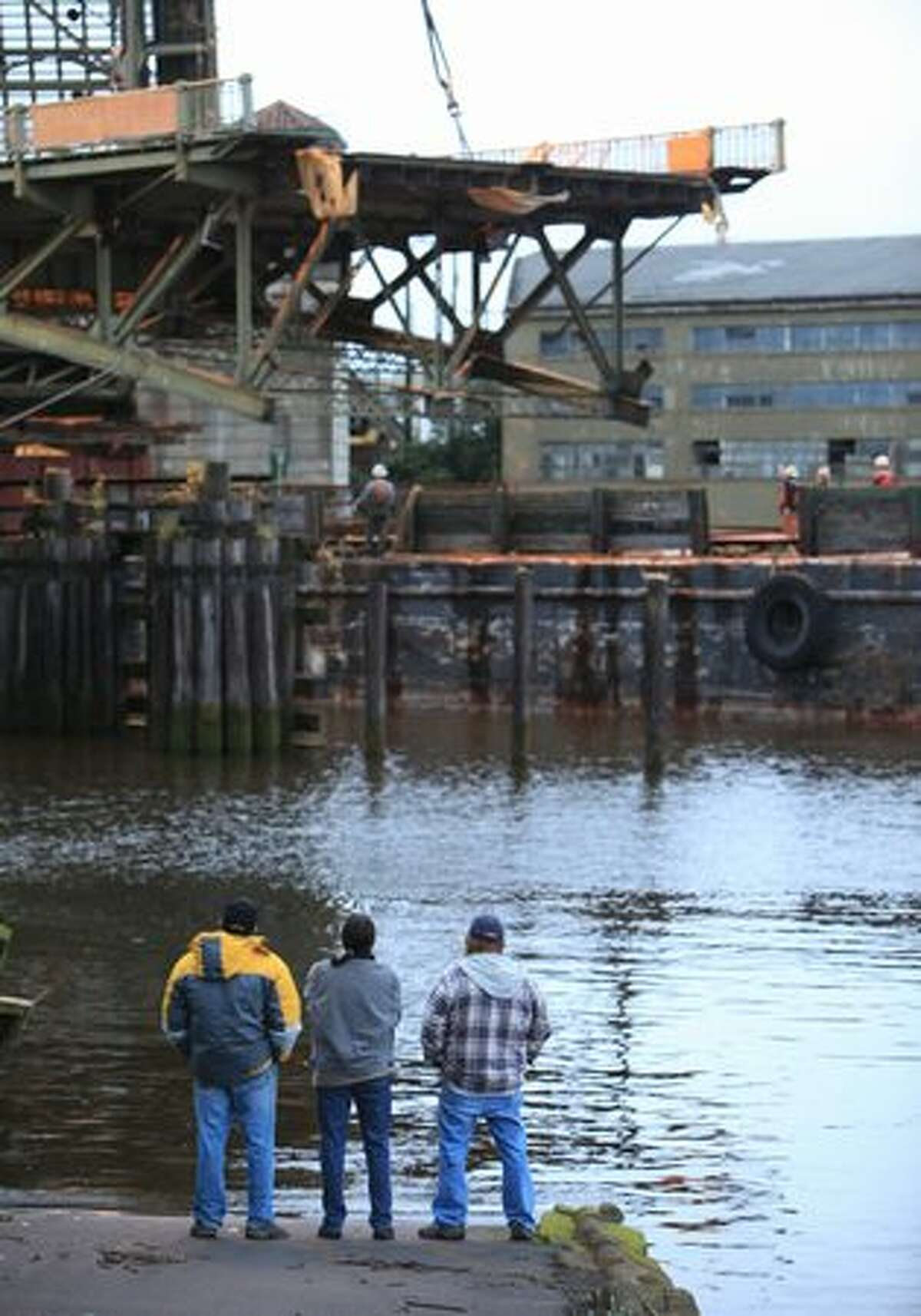 As neighborhood residents watch, the west leaf of the South Park Bridge is lowered onto a barge on the Duwamish River.