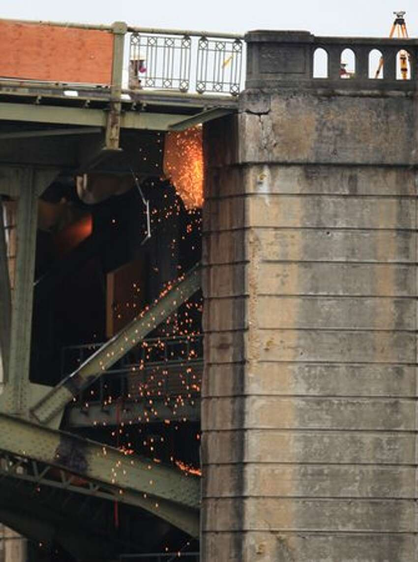 Sparks fly as as the west leaf of the South Park Bridge is cut from the west bridge tower.