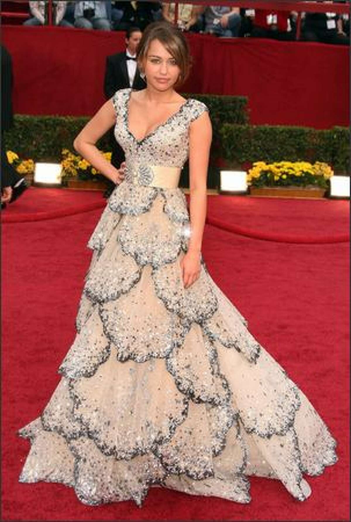 AP: Miley Cyrus' beaded Zuhair Murad dress was mostly white but had tiers of midnight-blue beaded petals.