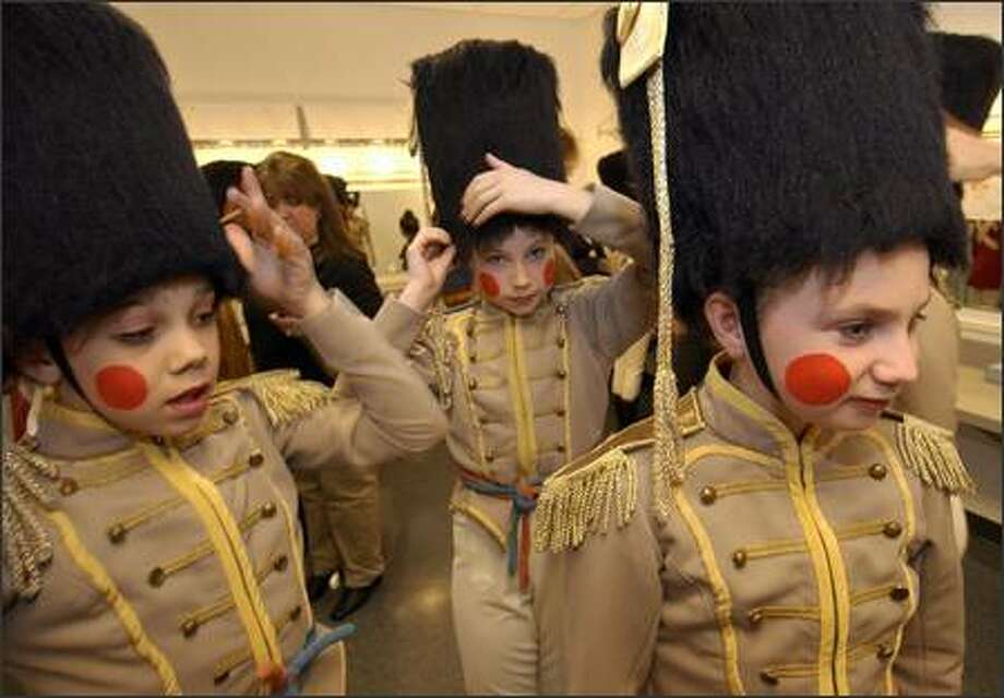 Adjusting their soldier hats, Rachel Schneider, left, Camilla Cyr, center, and Kate Collins prepare to hit the stage for a dress rehearsal. Photo: Ron Wurzer, Seattle Post-Intelligencer