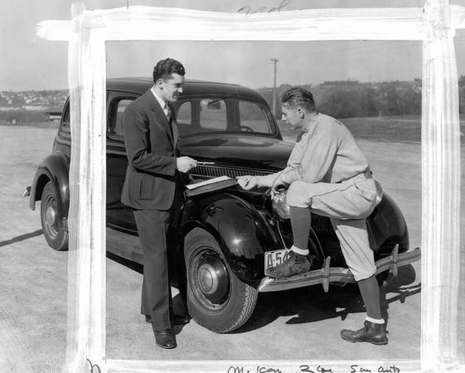 The undated photo caption read: Bill Smith, ex-University of Washington football star and All-American, discusses William O'McKay's fourth annual free season ticket campaign with Jimmie Phelan, Husky coach. Smith is on the McKay sales staff. Photo: P-I File