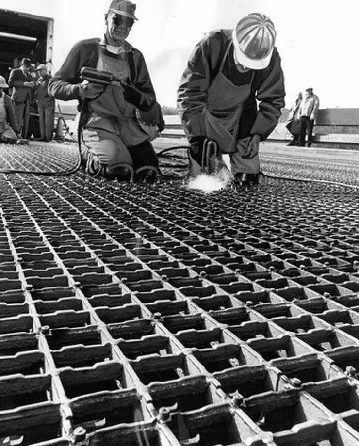 Ironworkers Whitey Wallace (left) and Roy Garrison weld studs on steel deck of First Avenue South Bridge - a safety feature designed to reduce automobile skidding. March 23, 1964. Photo: P-I File