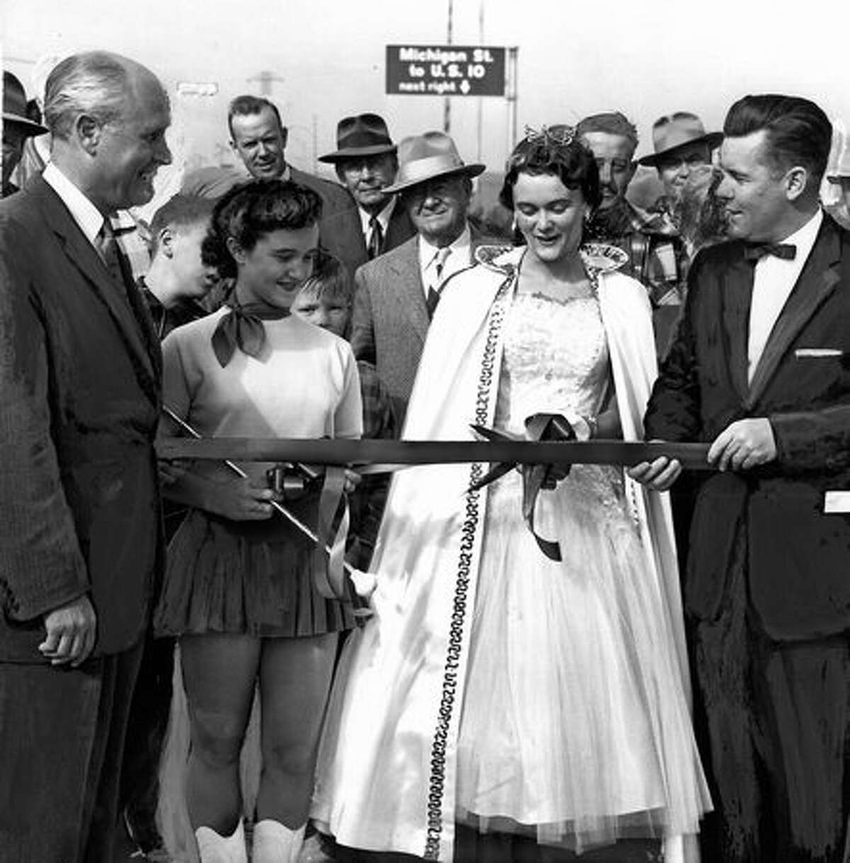 The September 1956 photo caption read: Gov. Arthur R. Langlie (left) and Mayor Gordon S. Clinton are shown here with the girls they chose to do the ribbon cutting at the opening of the new First Avenue South Bridge. Doing the cutting are (left) Billie Lee Westcott, 14, drum majorette and mascot of the Highline High School band, and Carol Hawkinson, 18, Miss Southwest Seattle.