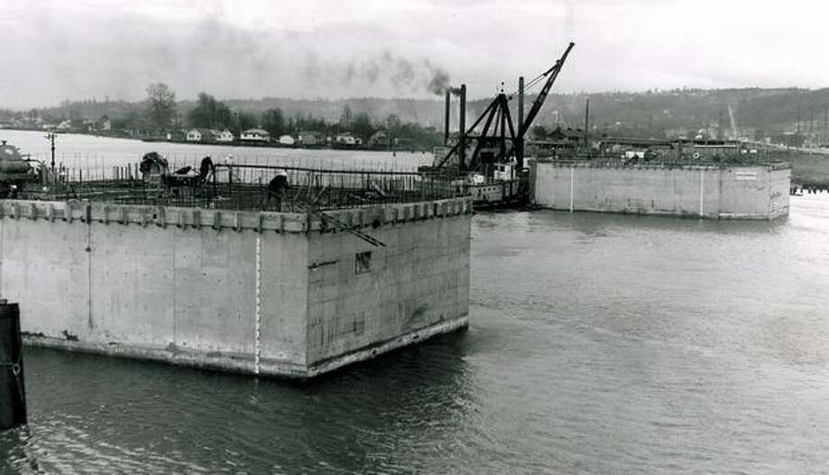 The February 1955 photo caption read: These two concrete piers, shown here being floated into place, will support the new First Avenue South bridge over the Duwamish Waterway when the bridge is completed. The two-unit pier will be sunk in the waterway and more concrete will be poured on top. Note size of pier in relation to tug alongside. Photo: P-I File