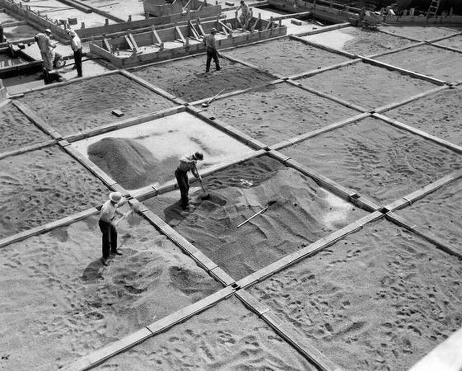 Workmen spread coarse gravel between forms, August 11, 1954. Photo: P-I File