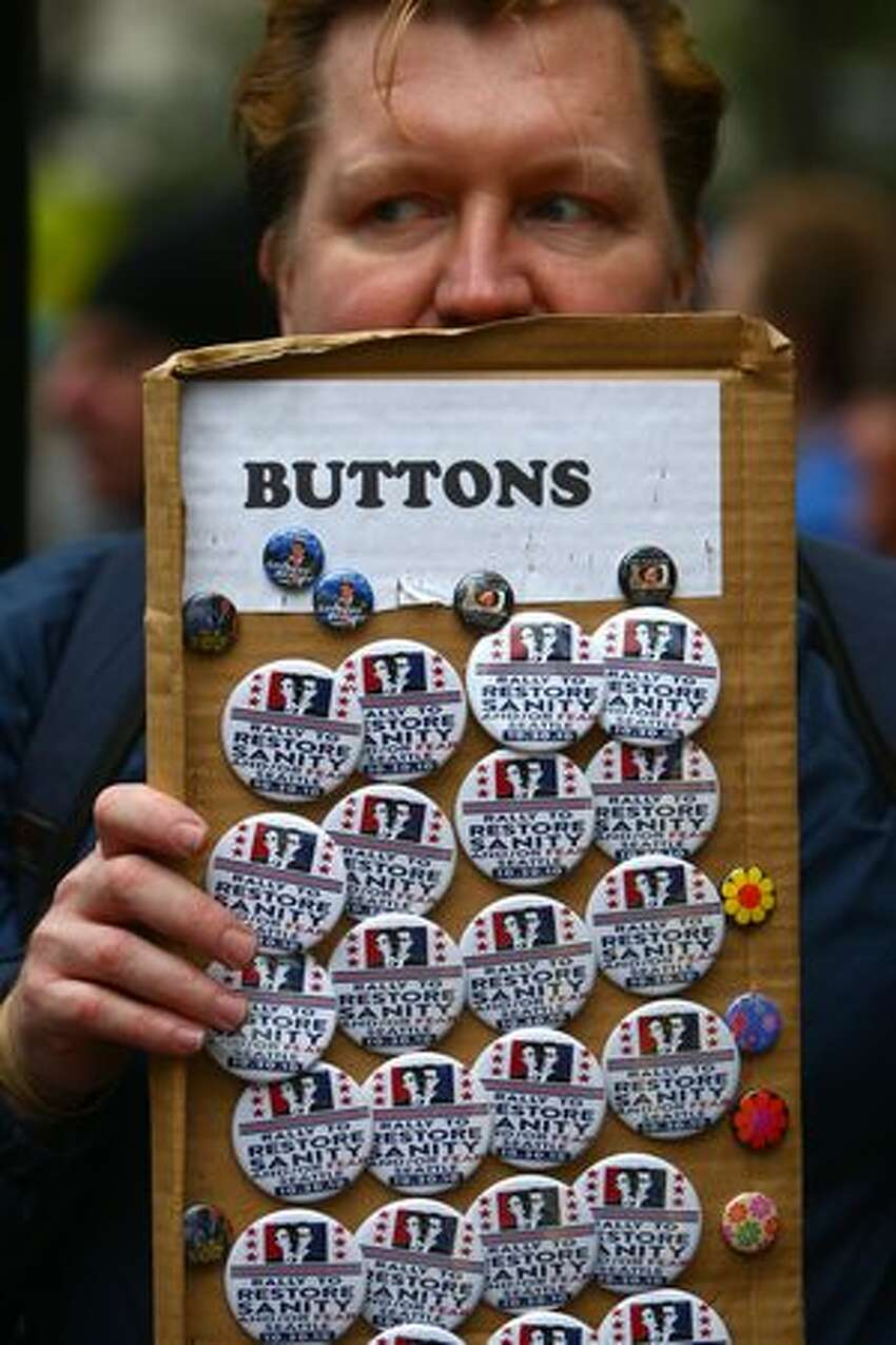 Chad Smith sells commemorative buttons at Westlake Park in Seattle during a satellite gathering of the Rally to Restore Sanity.
