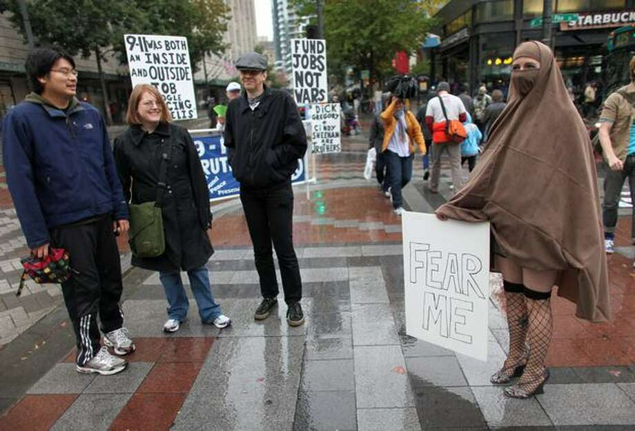 Rachel Jackson, right, wears a head-covering and holds a sign at Westlake Park in Seattle during a satellite gathering of the Rally to Restore Sanity. Photo: Joshua Trujillo, Seattlepi.com