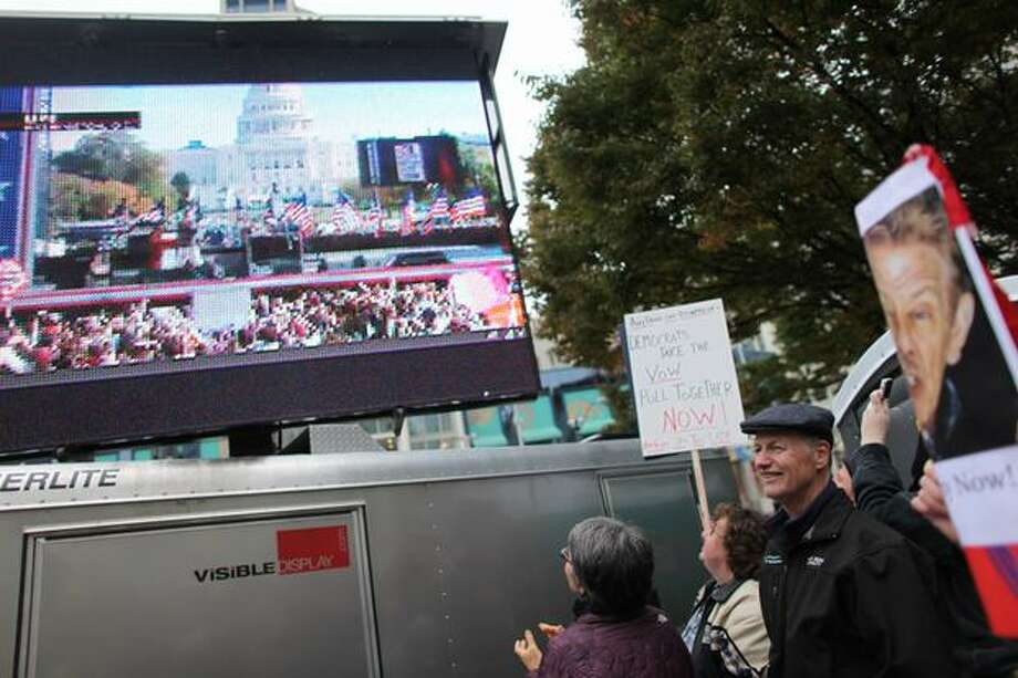 People watch the Rally To Restore Sanity on a large television at Westlake Park in Seattle. Photo: Joshua Trujillo, Seattlepi.com