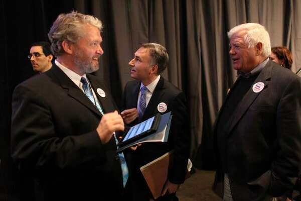 Washington State Democratic Party Executive Director Jaxon Ravens, left, King County Executive Dow Constantine and U.S. Rep. Jim McDermott look at election results during an election return party on Tuesday in Seattle.