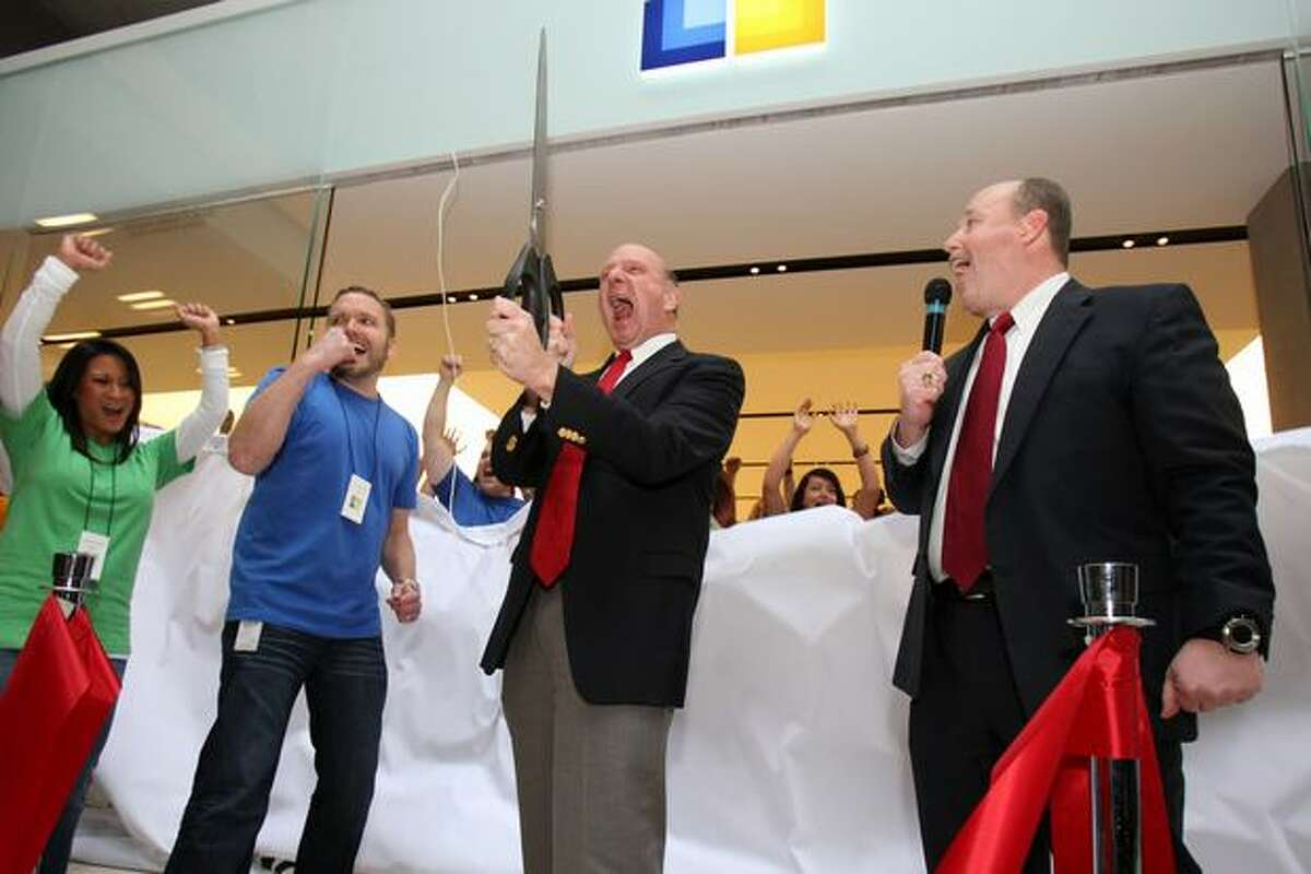 Microsoft CEO Steve Ballmer, center, and COO Kevin Turner, right, cut a ribbon as a curtain reveals the new Microsoft Store during the opening Nov. 18, 2010, at Bellevue Square mall.