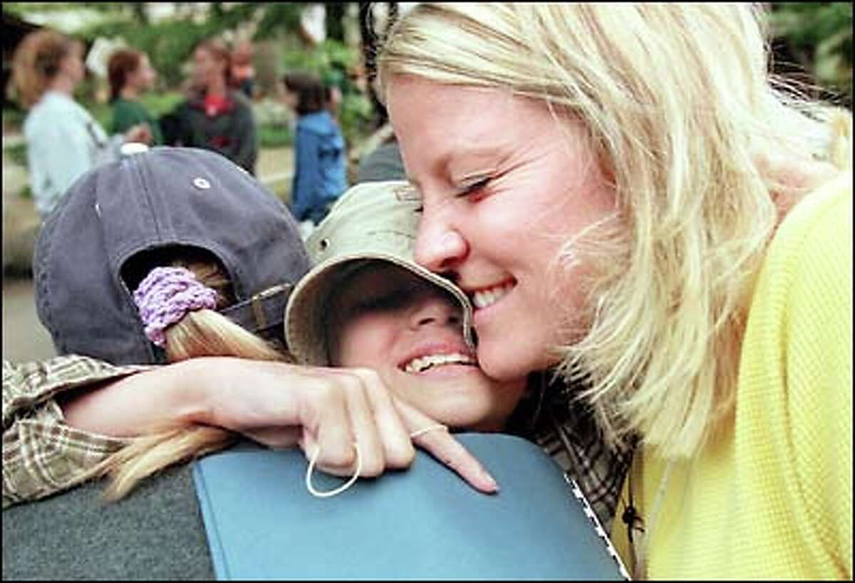 Hugs, smiles and tears all come together as camp ends. Lisa holds tight to counselors Tessie Baird, left, and Leslie Selig.
