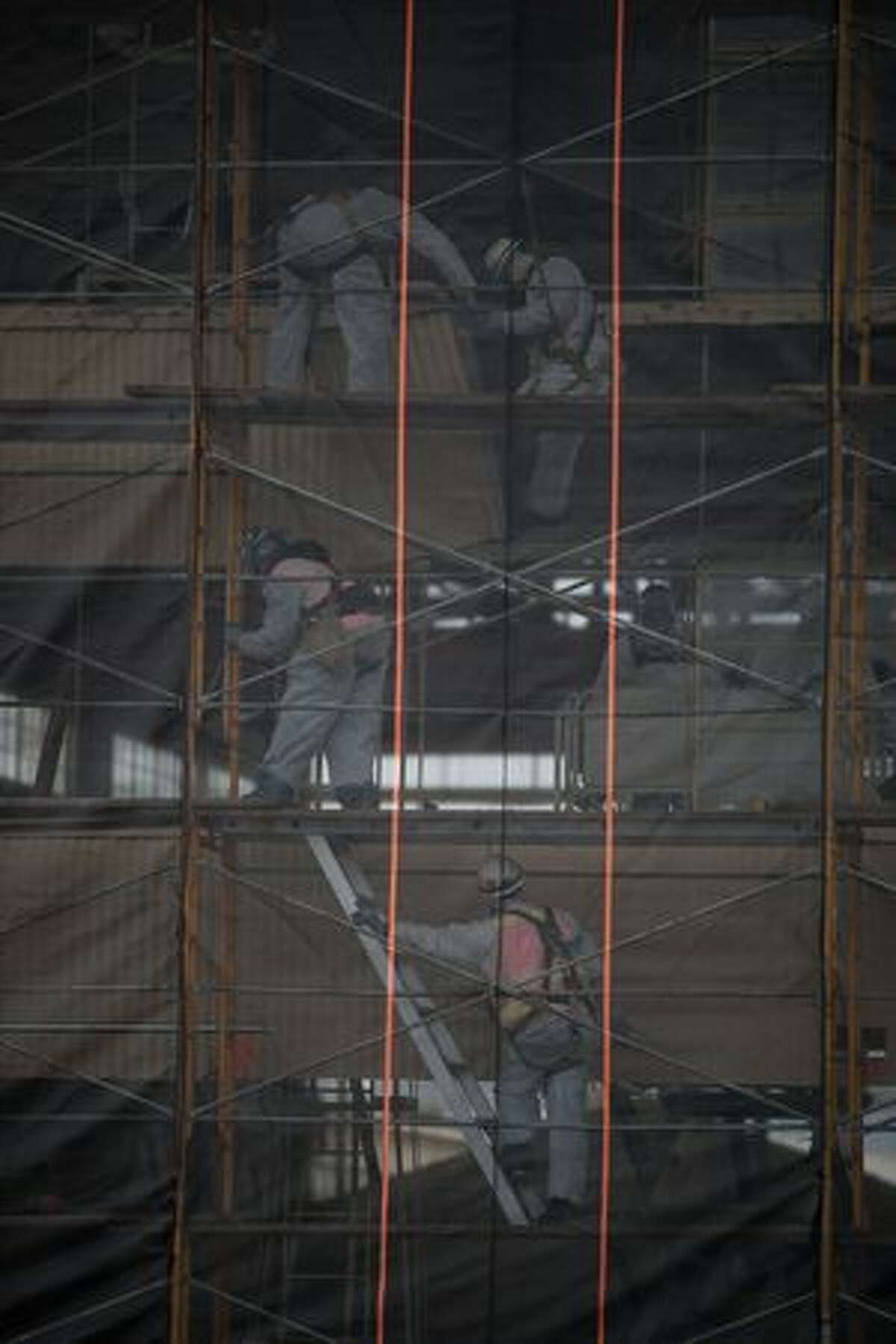 Workmen use scaffolding to begin tear down of Boeing's Plant 2. Netting keeps debris from falling into the Duwamish Waterway below.