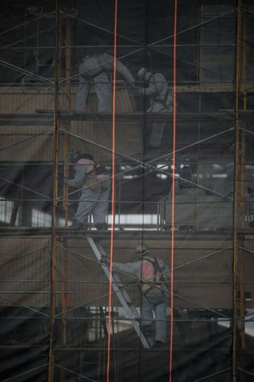 Workmen use scaffolding to begin tear down of Boeing's Plant 2. Netting keeps debris from falling into the Duwamish Waterway below.