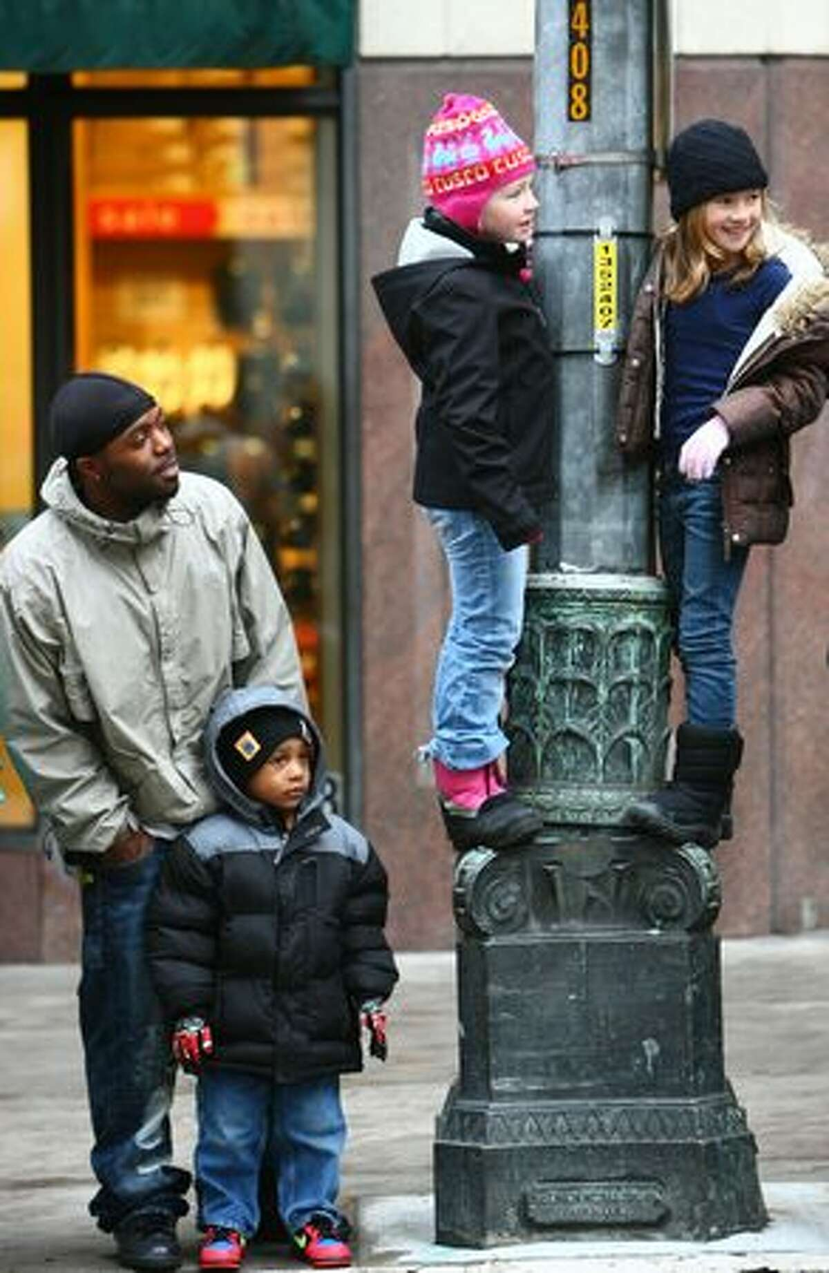 Spectators watch the Macy's Holiday Parade in downtown Seattle on Friday. Thousands came out for the annual event early Friday morning.
