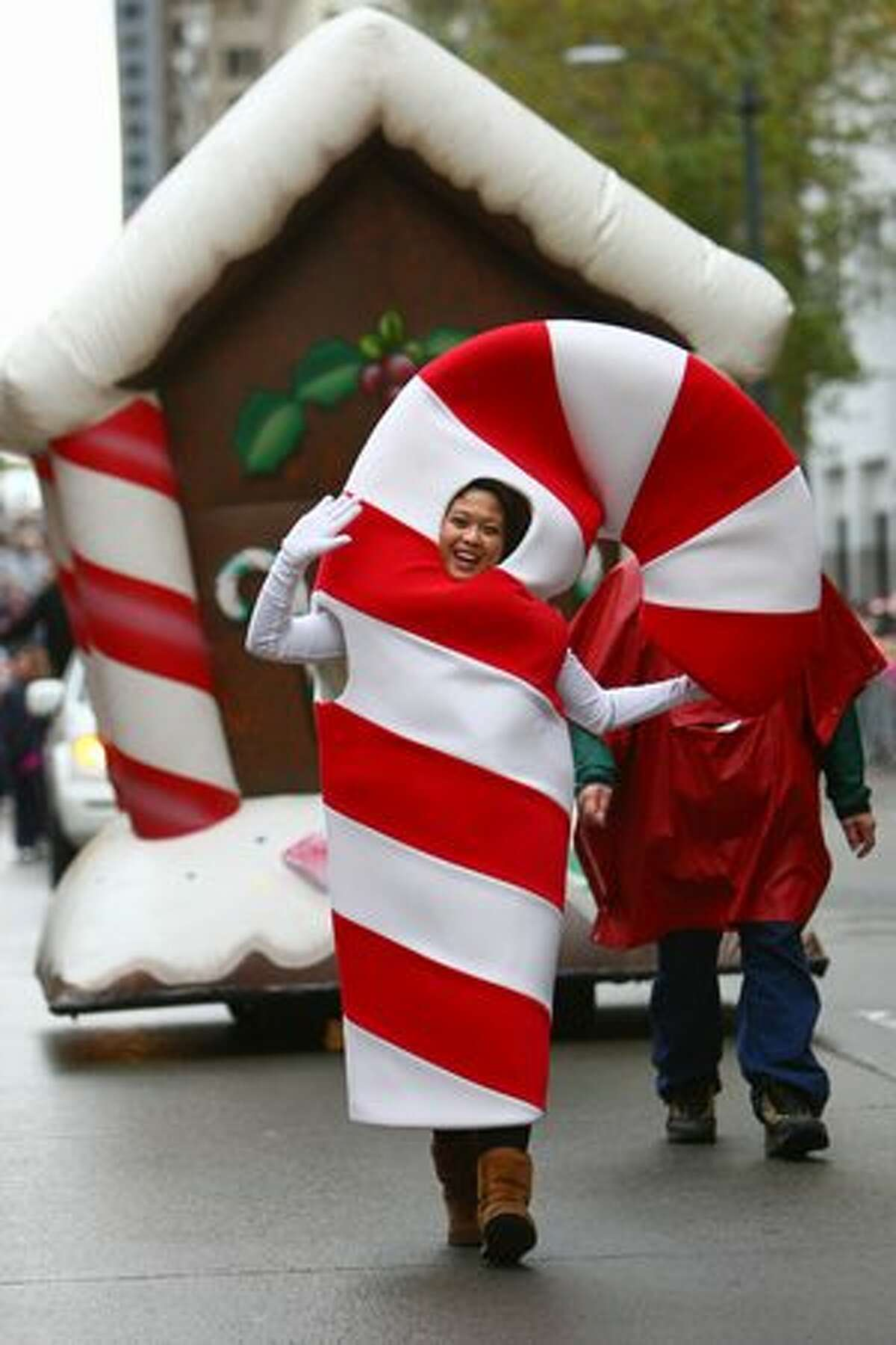 """A """"candy cane"""" walks along 4th Avenue during the Macy's Holiday Parade in downtown Seattle on Friday. Thousands came out for the annual event early Friday morning."""