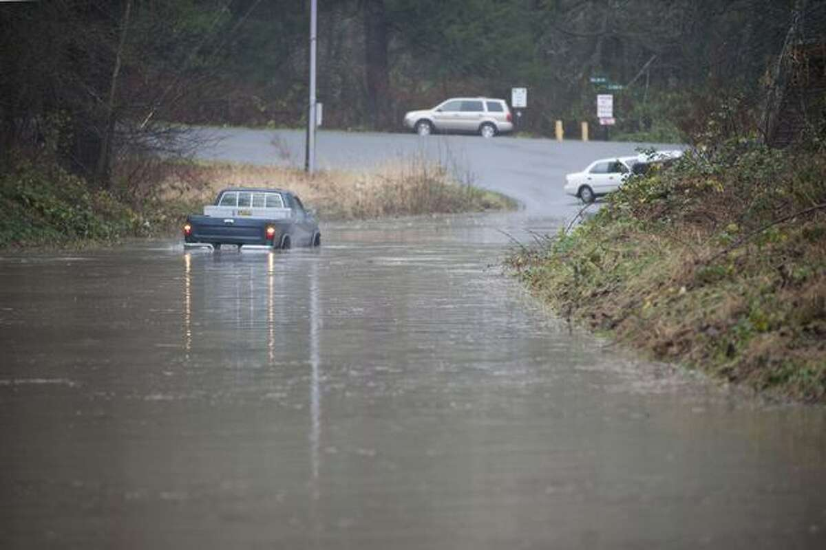 Drivers attempt to travel flooded roads in Snoqualmie on Monday.