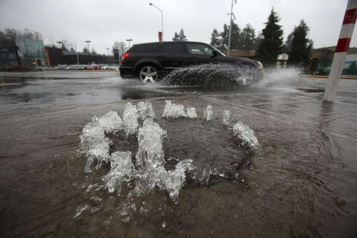 A sewer drain backs up, pouring raw sewage into Lake City Way in Seattle on Sunday as significant rain threatens to flood area rivers and low-lying areas.