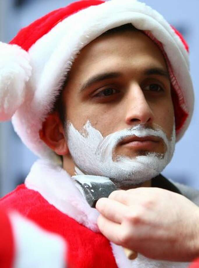 "Saurabh Sanghvi applies a ""beard"" during SantaCon on Saturday. Photo: Joshua Trujillo, Seattlepi.com"