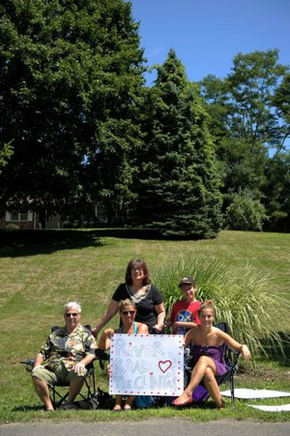 Rhinebeck residents (front row L-R) Norman Gastman, Rachael Scorca, Harleigh Gastman, (back row L-R) Amy Scorca and Uri Rooselaar hold up a sign showing their support as the town prepares for the wedding of Chelsea Clinton and Marc Mezvinsky on July 31, 2010 in Rhinebeck, New York.