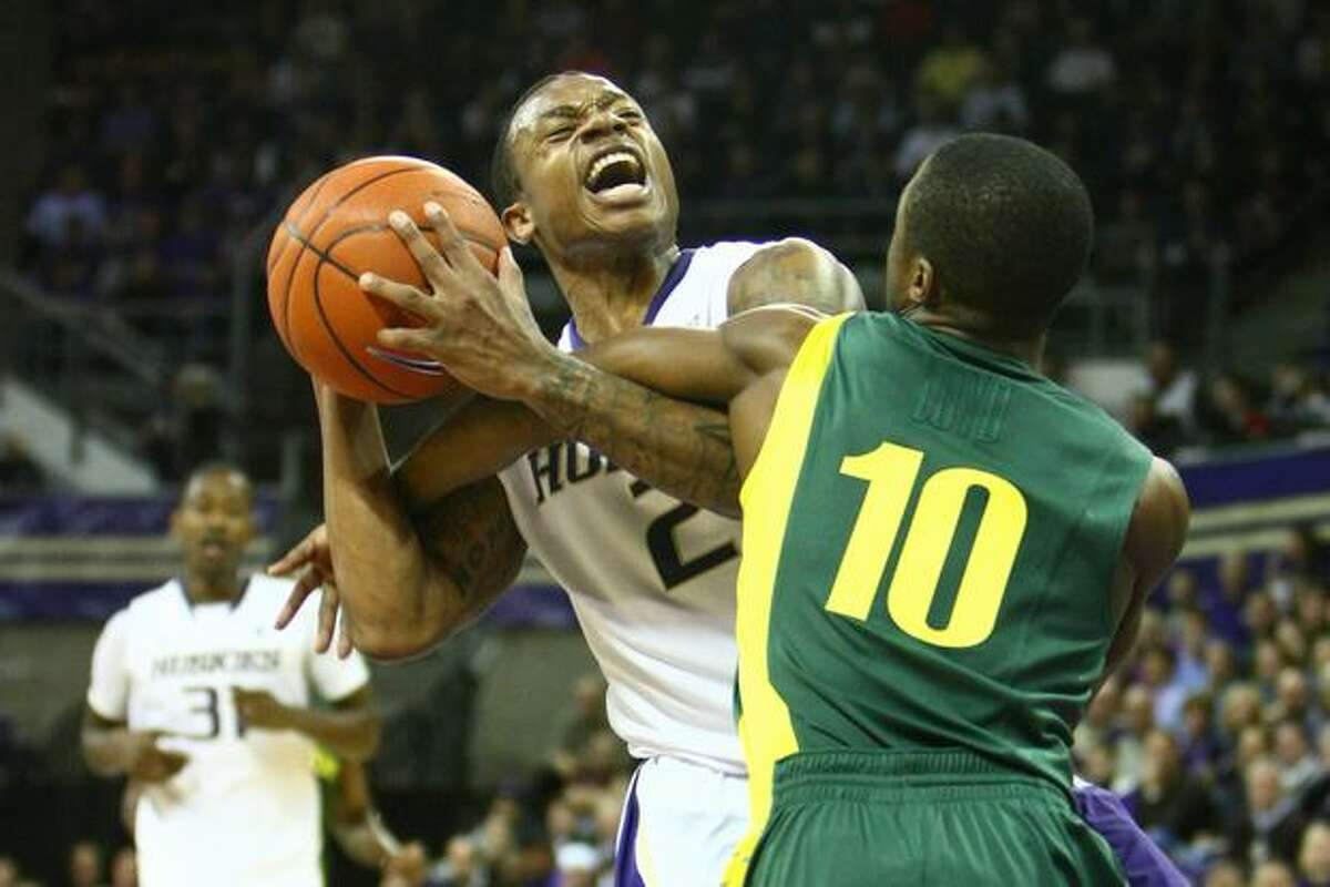 Washington's Isaiah Thomas is fouled by Oregon's Johnathan Loyd in the second half of the teams' Pac-10 Conference game at Hec Ed Pavilion in Seattle on Thursday, Jan. 6, 2010.