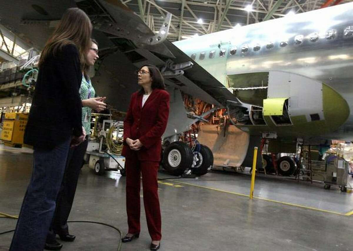U.S. Sen. Maria Cantwell, D-Wash., (right) talks with Boeing 767 employees Anna Karsky (left) and Maeghan Smith Hudon below the wing of a 767 at Boeing's plant in Everett Wash.
