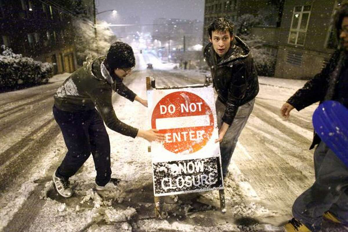 People place a road closure sign on East Denny Way in Seattle's Capitol Hill neighborhood on Tuesday, January 11, 2011 as snow blankets Seattle. The treacherous hill is a favorite spot for sledders and also a place where cars regularly careen out of control.