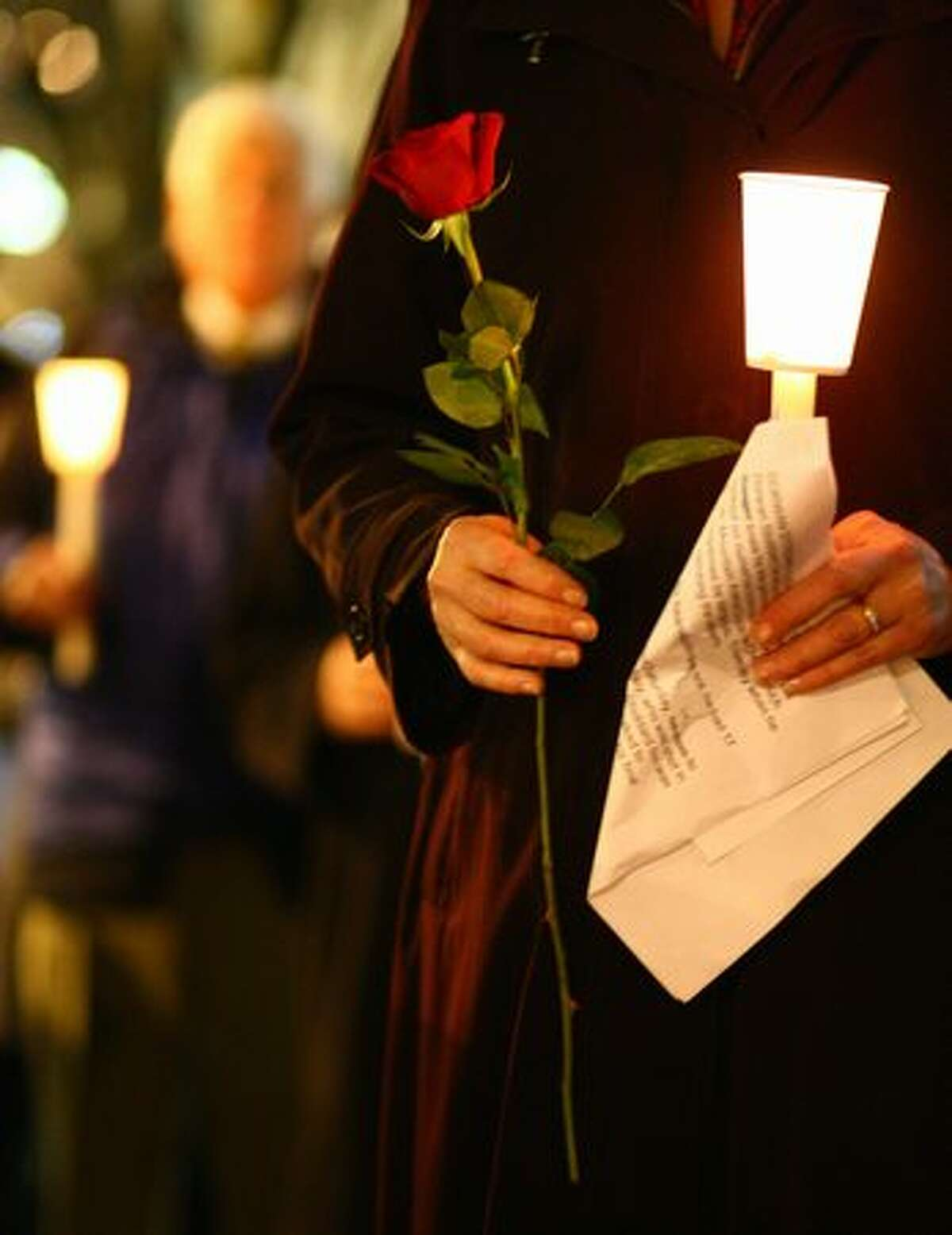 A participant holds a candle and rose at Seattle's Westlake Park.