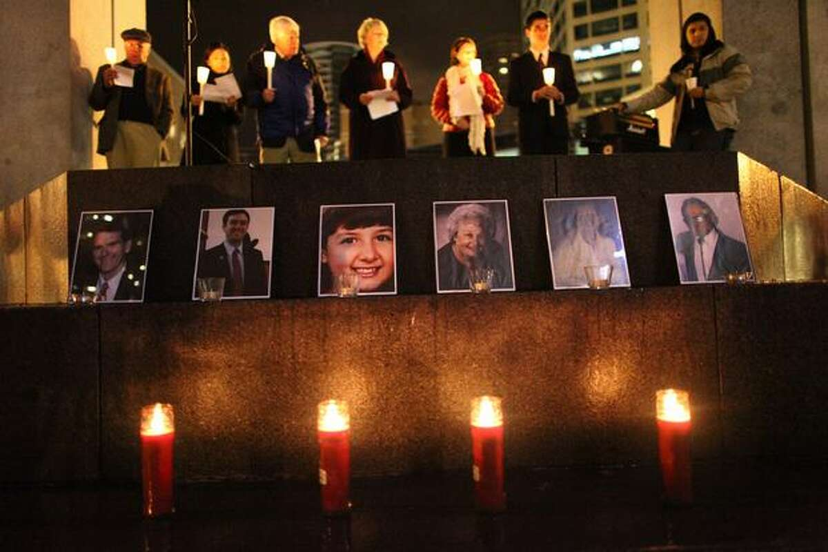 Pictures of Tucson shooting victims are placed near candles during a memorial at Seattle's Westlake Park on Thursday, Jan. 13, 2011. Last Saturday's shootings stunned the nation and prompted an outpouring of support for the victims and their families.