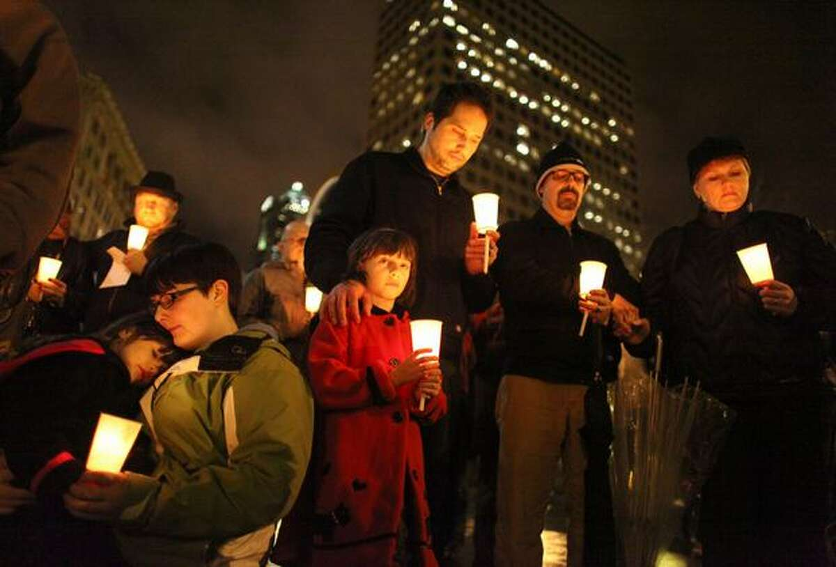 From left, Ava Picasso, 4, Amber Miller, Livia Picasso, 6, Brent Picasso, Scott Miller and Karina Miller hold candles during a memorial at Seattle's Westlake Park. Ava and Livia are great-granddaughters of 76-year-old Dorwan Stoddard, a former Sequim resident who was killed during the rampage in Tucson.