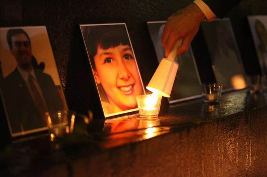 A candle is lit in front of a photograph of 9-year-old shooting victim Christina Taylor Green during a memorial at Seattle's Westlake Park. Photo: Joshua Trujillo, Seattlepi.com