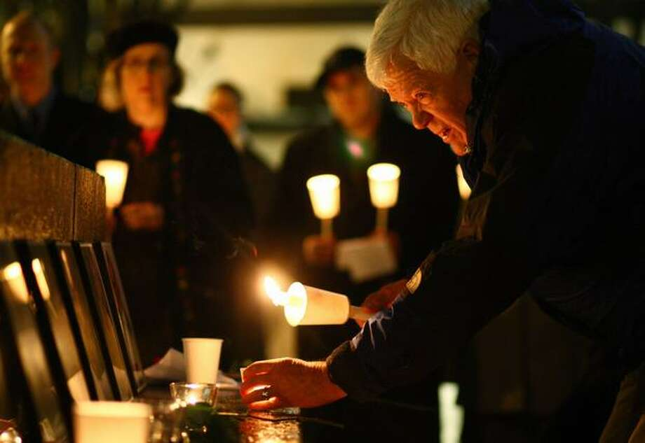 U.S. Rep. Jim McDermott lights a candle during a memorial at Seattle's Westlake Park for victims of the Tucson shooting rampage. McDermott said at the rally that he had known for weeks that a Calfornia man, arrested Wednesday, had threatened him with death. Photo: Joshua Trujillo, Seattlepi.com