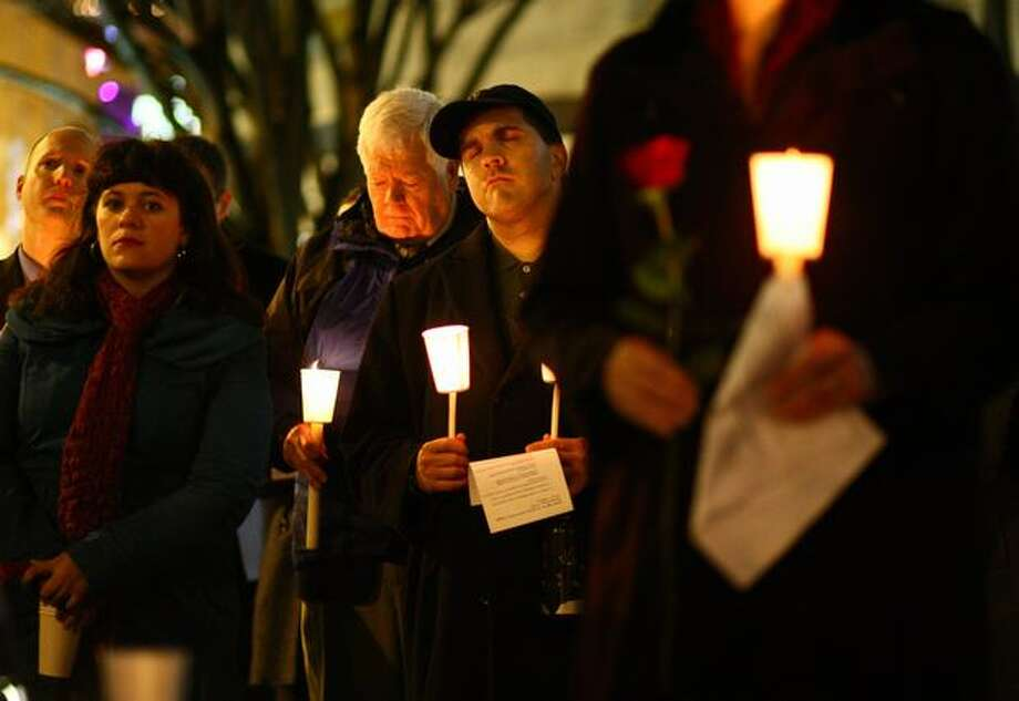 Mourners, including U.S. Rep. Jim McDermott, center left, observe a moment of silence during a memorial at Seattle's Westlake Park. Photo: Joshua Trujillo, Seattlepi.com
