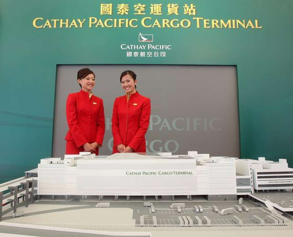 Models pose beside a model of the new Cathay Pacific cargo terminal at Hong Kong International Airport
