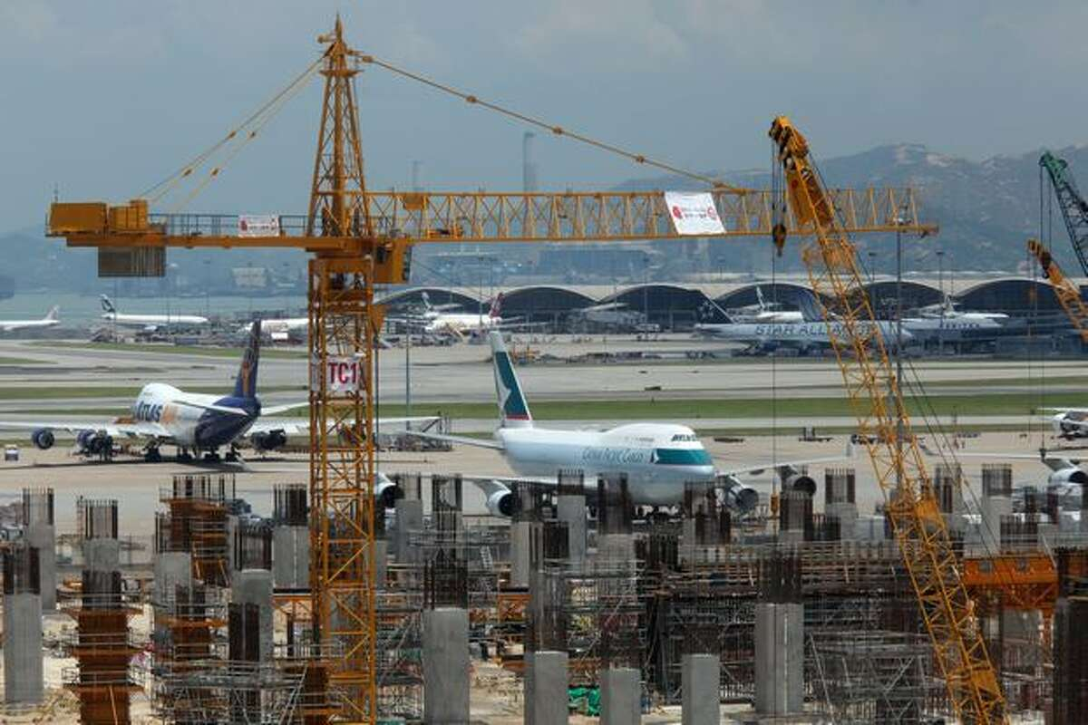 A Cathay Pacific cargo aircraft sits parked behind the site of the company's new cargo terminal at Hong Kong International Airport