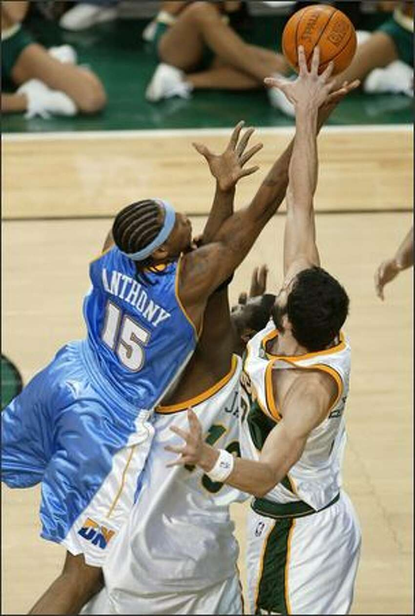 Denver's Carmelo Anthony, who hit the winning shot, drives through two Sonics en route to the basket.