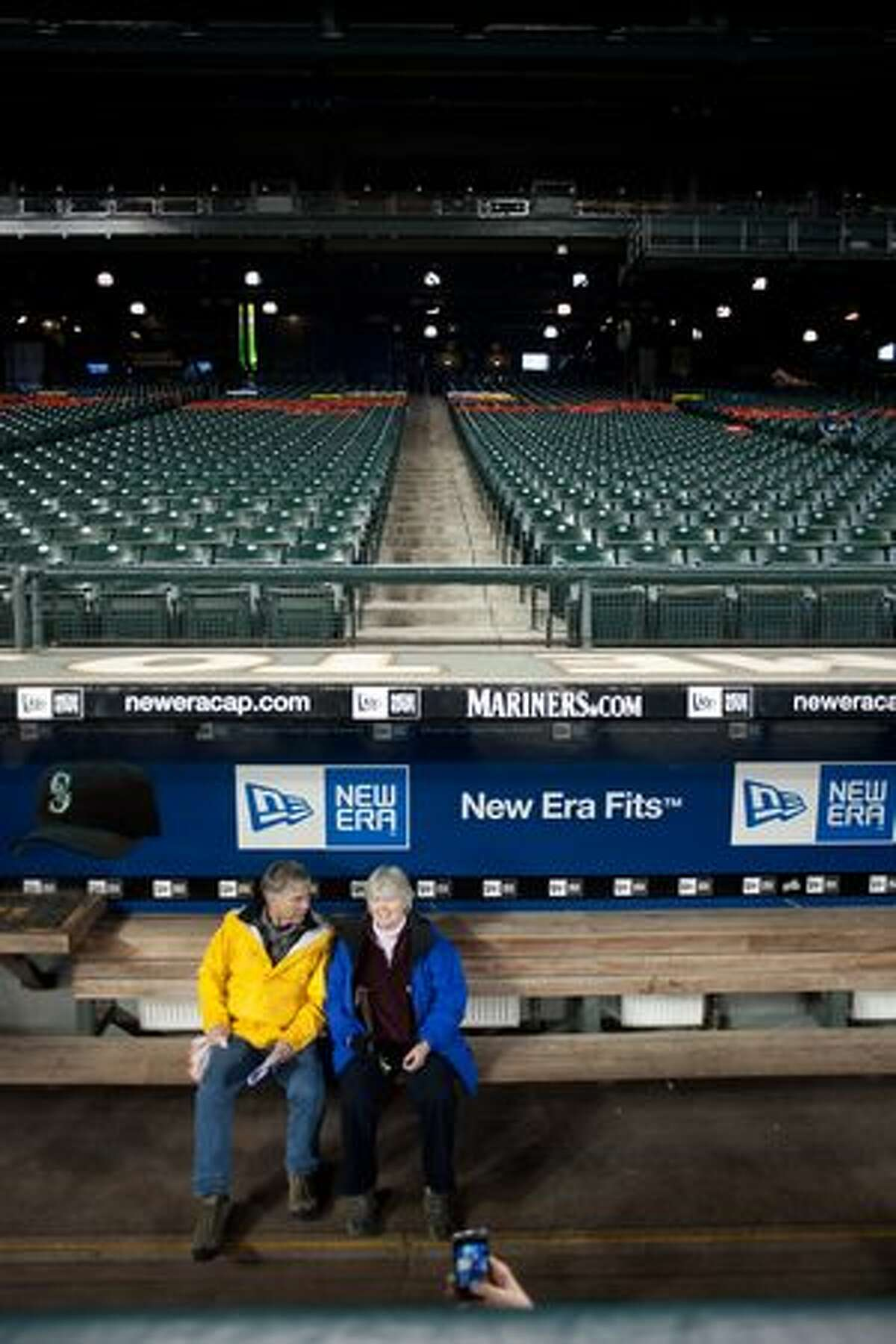 Husband and wife take a picture for the kids in the dugout.