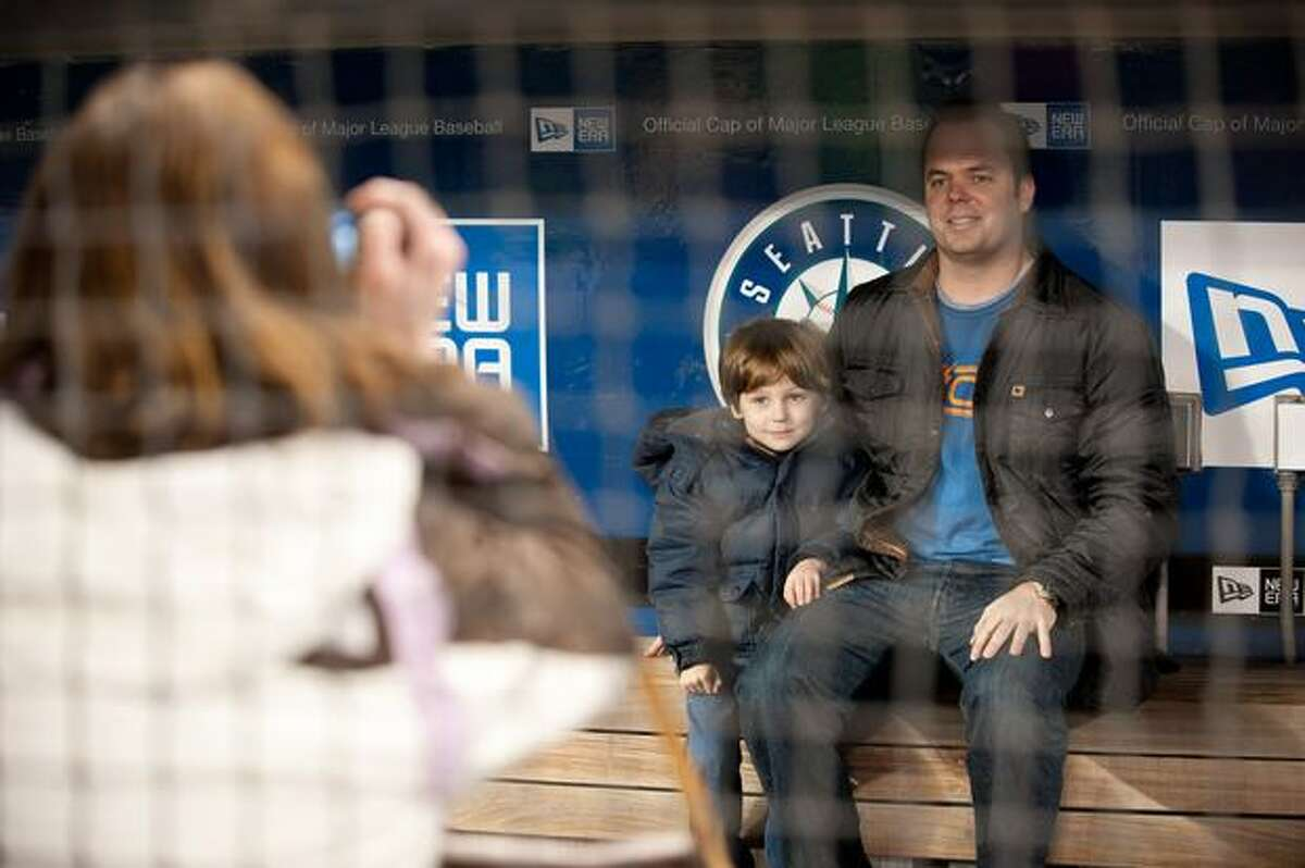Greg and Ryder York take a picture in the dugout at Safeco Field as part of the annual Mariners Fanfest, Saturday, Jan. 29, 2011.