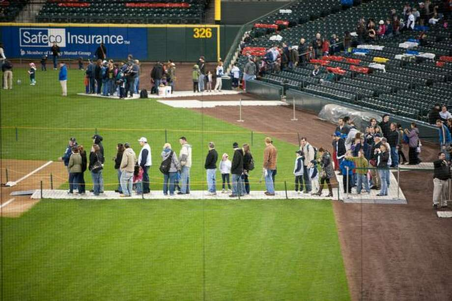 Mariners fans line up on the field for games and activities. Photo: Elliot Suhr, Seattlepi.com