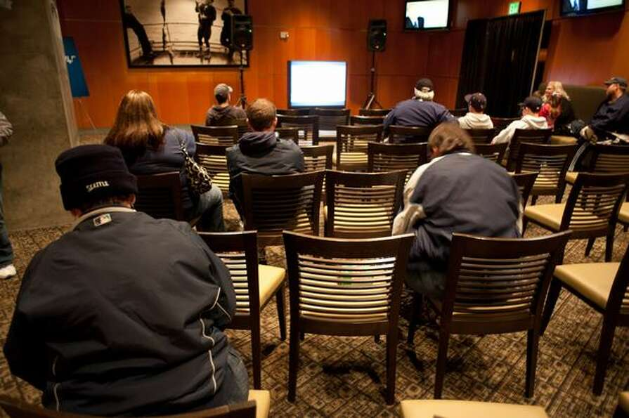 Fans sit and watch clips of Dave Niehaus' broadcast calls, life and memorial service in the exhibit.