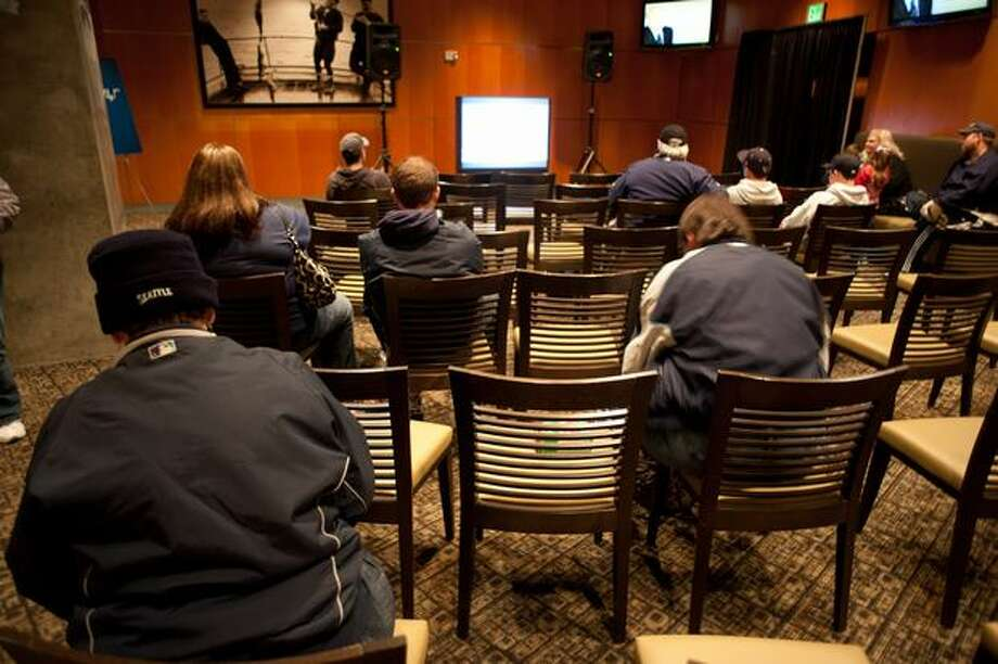 Fans sit and watch clips of Dave Niehaus' broadcast calls, life and memorial service in the exhibit. Photo: Elliot Suhr, Seattlepi.com