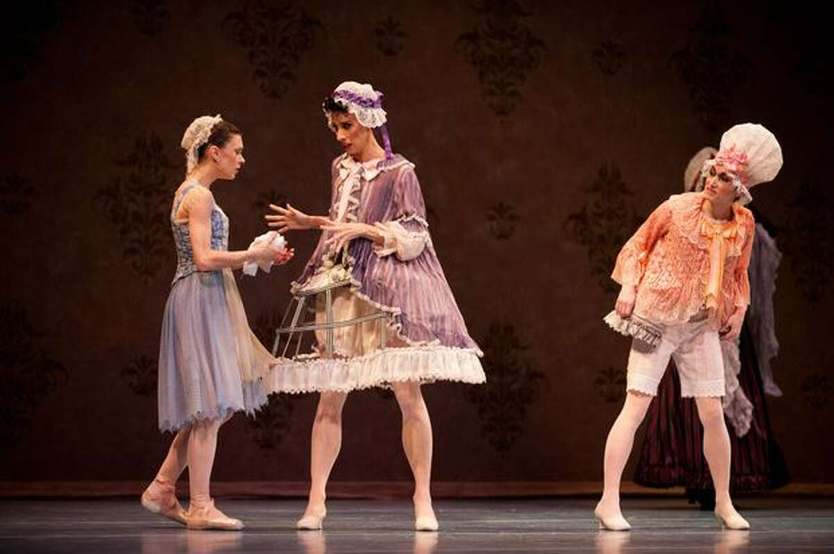 """The Pacific Northwest Ballet presents """"Cinderella."""" Cinderella, played by Rachel Foster, is handed a rag by her stepsister. Linsdsi Dec, left, and Chalnessa Eames, right, play the stepsisters. The show premieres on Friday, February 4, at McCaw Hall."""