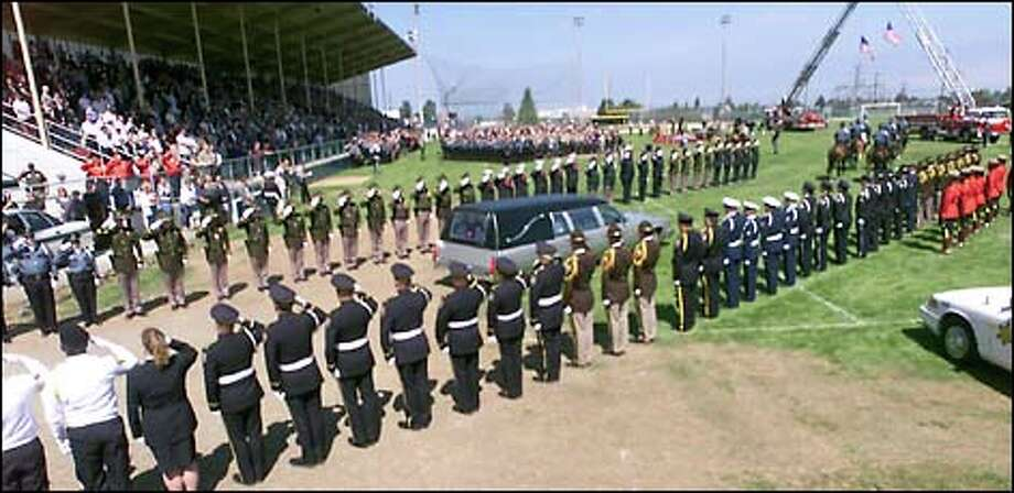 The hearse is led into Port Angeles' Civic Field by the traditional riderless black horse, empty boots reversed in its stirrups, filing past two columns of Wallace Davis' fellow officers.  Police from throughout the region attended. Photo: Grant M. Haller, Seattle Post-Intelligencer