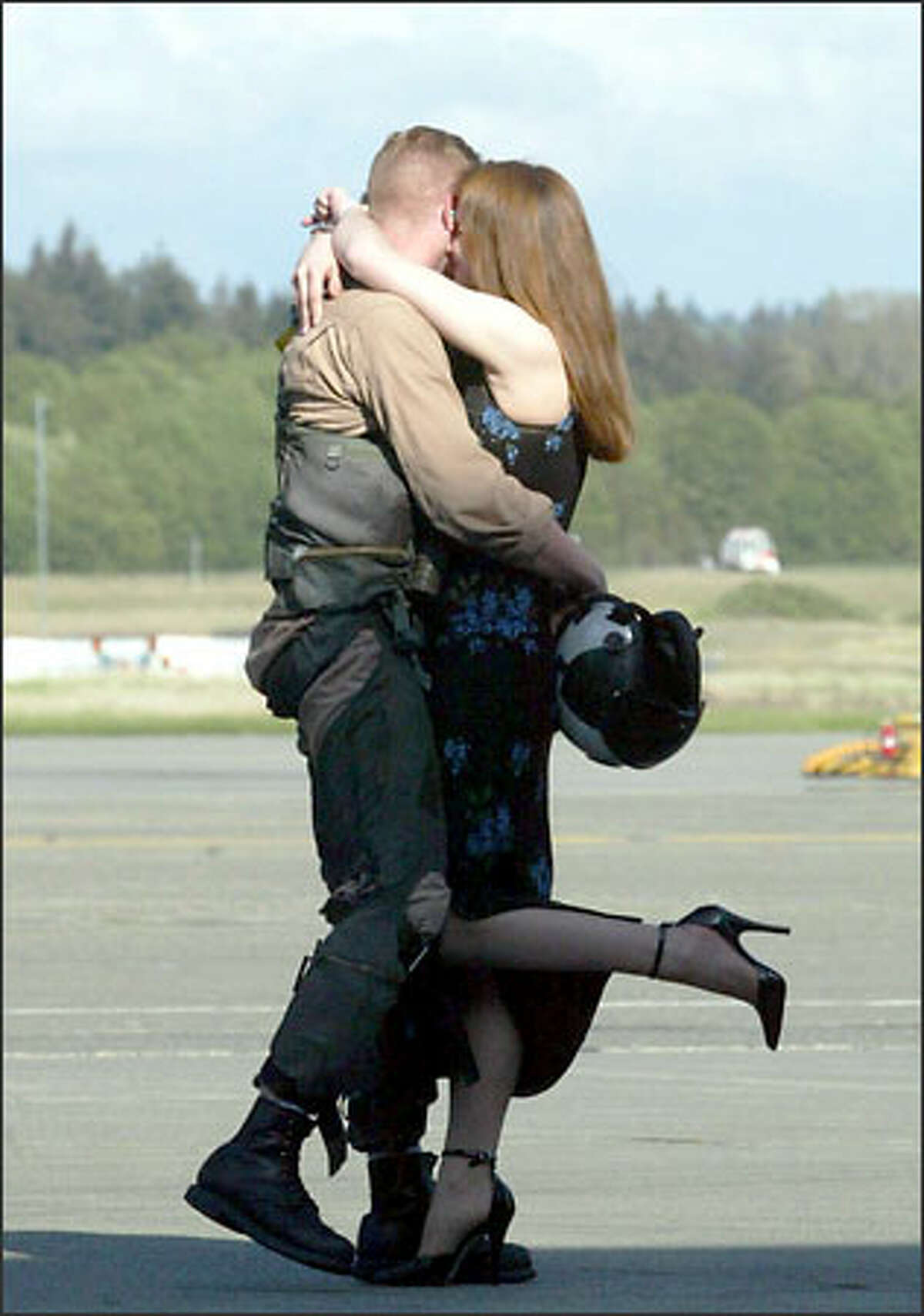 Lt. Jeff Barrett, an EA-6B Prowler pilot, embraces his wife, Kate, after arriving at Whidbey Island Naval Air Station.Schenker: