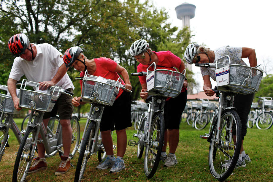 Glenn Jensen (from left), Vicki Roberson, Vicki Smith and Bonnie Barstow look at the extra lock on their rental bikes as they prepare to ride downtown. Photo: LISA KRANTZ/lkrantz@express-news.net / SAN ANTONIO EXPRESS-NEWS