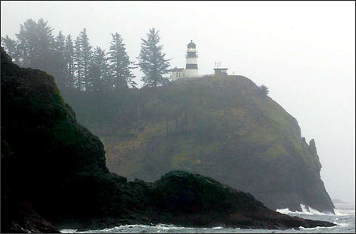 Low clouds shroud the coast as the Cape Disappointment Lighthouse flashes its beacon. This was the kind of wet weather that the Lewis and Clark expedition found when they reached the Long Beach Peninsula in November 1805.